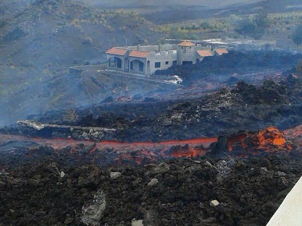 The lava flow of Fogo passing near a destroyed building (image: INVOLCAN / @involcan / twitter)