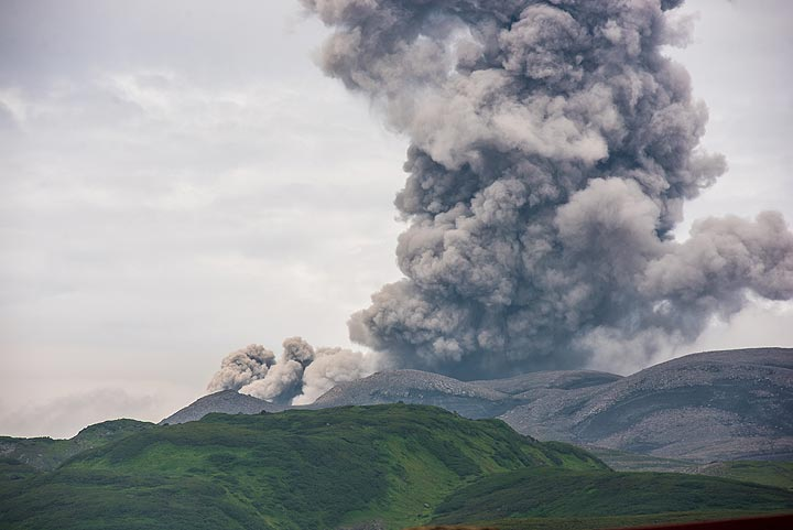 Strong explosion from Ebeko with 2 km ash plume and pyroclastic flow towards the left seen from Severo Kurilsk town at 10:30 local time on 20 July 2019 (image: Tom Pfeiffer / VolcanoDiscovery)