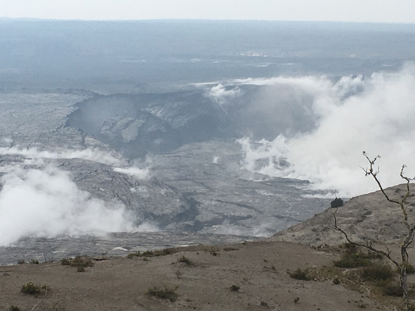 Photograph showing the inward slumping of Halema'uma'u crater rim and walls in response to ongoing subsidence of Kilauea's summit. This view to the southwest, taken after the explosion that occurred on the morning of 16 June, a section of dark-coloured wall rock (center left) has detached and dropped downward into the crater. (HVO/USGS)